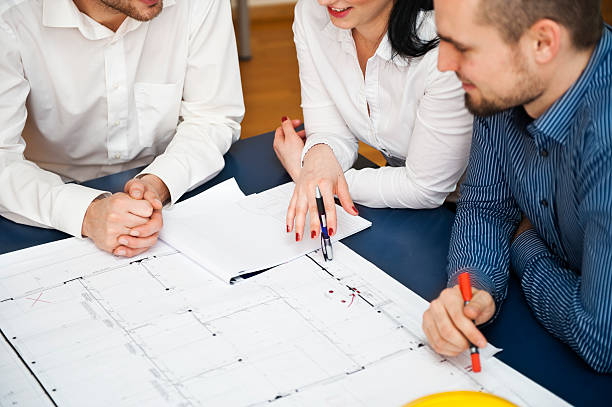 Architecte qui élabore les plans d'une maison avec ses clients