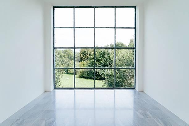 Grande pièce vide avec une immence baie vitrée donnant sur la nature