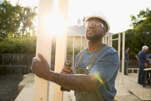 Ouvrier en train de transporter des planches de bois pour construire une maison passive