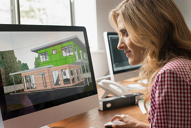 Femme qui regarde des plans de constructions sur un ordinateur